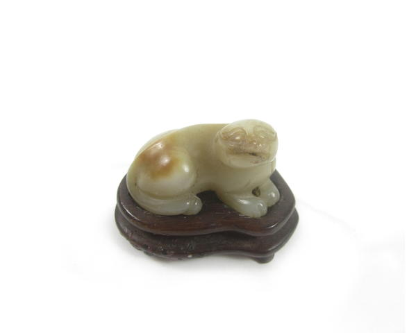 A carved jade lion-dog and wood stand (2)