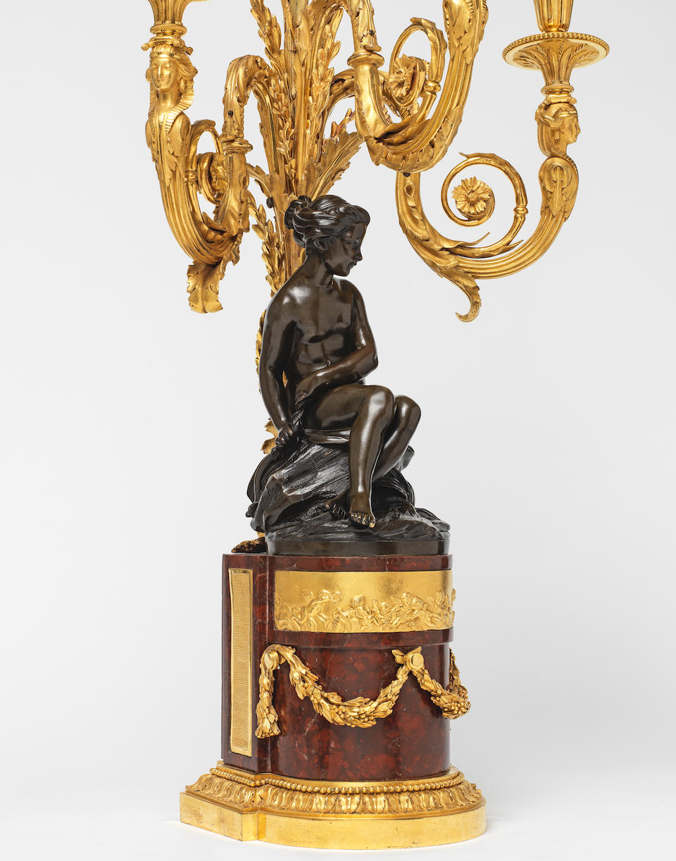 An important pair of Louis XVI gilt and patinated bronze and rouge griotte marble figural three light candelabra  circa 1785, the gilt bronze mounts attributed to Francois Réymond (French, c. 1745-1812), the figures of Cupid ('L'Amour Menacant') and a nymph ('La Nymphe') after the models by Etienne-Maurice Falconet (French, 1716-1791)  (2)